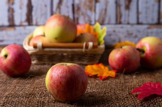 Спелые яблоки на мешковине и в корзине. деревенский стиль