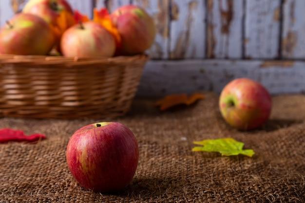 黄麻布とバスケットに熟したリンゴ。素朴なスタイル