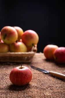 黄麻布とバスケットの熟したリンゴ