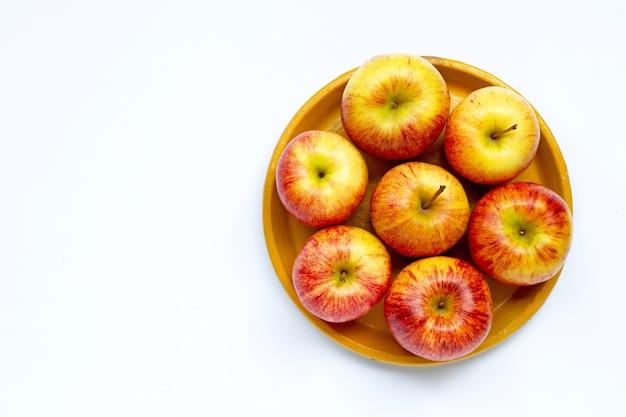 Спелые яблоки на желтой тарелке на белом фоне. копировать пространство