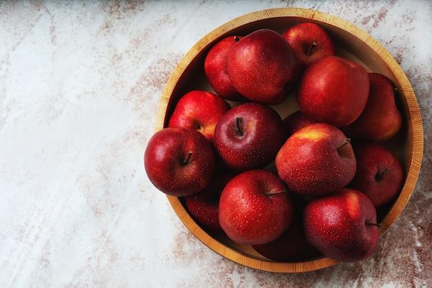Спелые яблоки в деревянной миске. концепция устойчивого хранения. вид сверху. плоская планировка