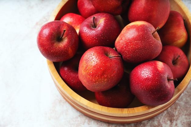 熟したリンゴが木製のボウルでスターキング。持続可能なストレージのコンセプト。