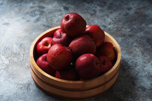 Спелые яблоки в деревянной миске. концепция устойчивого хранения.