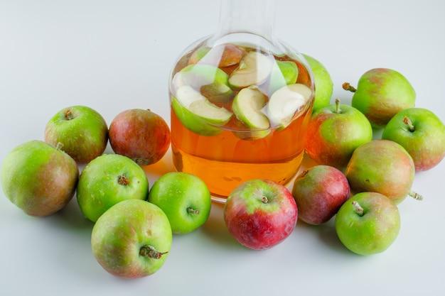 Спелые яблоки с напитком под высоким углом зрения на белом