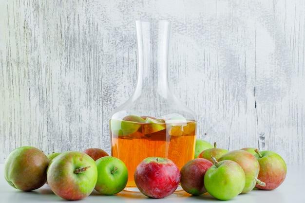 Спелые яблоки с напитком на белом и шероховатом, вид сбоку.