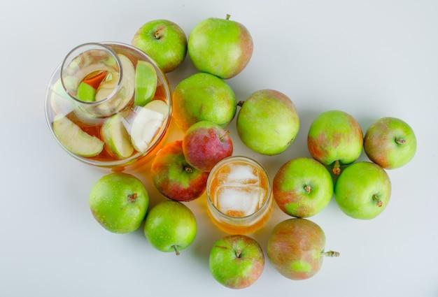 Спелые яблоки с ледяным напитком на белом