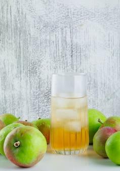 Спелые яблоки с ледяным соком, вид сбоку на белом и шероховатом