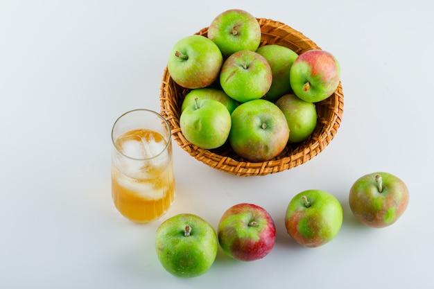 Спелые яблоки с соком в плетеной корзине на белом, высоком угле обзора.