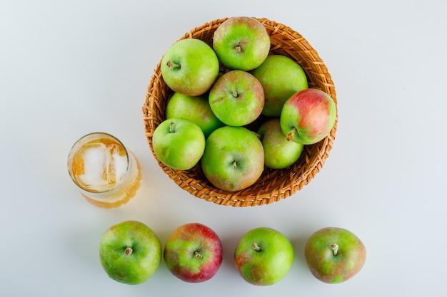 Спелые яблоки с соком в плетеной корзине на белом.