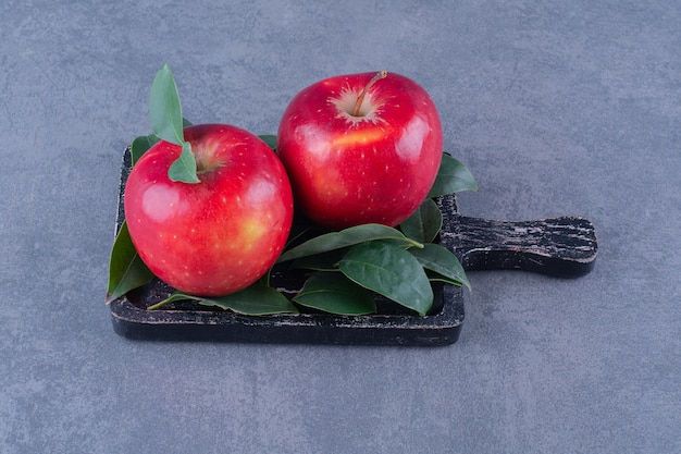 Ripe apples with leaves on board on the dark surface