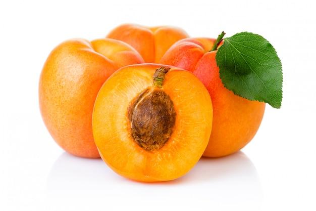 Спелые плоды абрикоса с зелеными листьями и ломтиком на белом