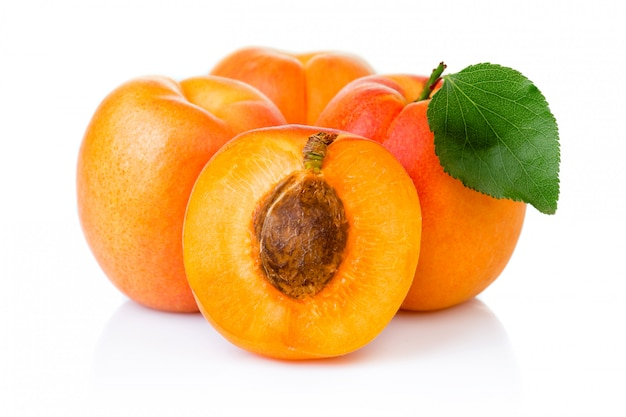 Ripe apricot fruits with with green leaf and slice isolated on white