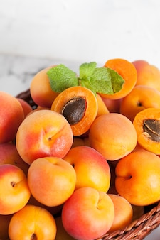 Ripe apricots in a basket on a light surface