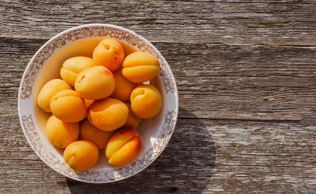 Спелые абрикосы в деревенской тарелке на столе, на деревянном фоне