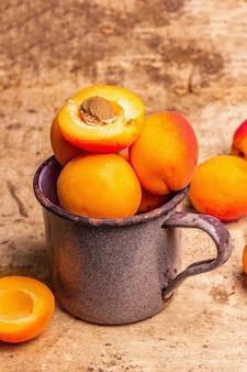 빈티지 철 머그에 익은 살구. 달콤한 과일, 오래된 나무 테이블, 클로즈업