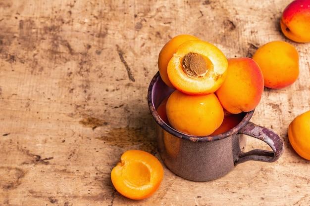 빈티지 철 머그에 익은 살구. 달콤한 과일, 오래된 나무 테이블, 복사 공간