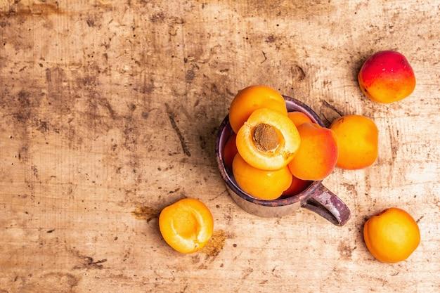 빈티지 철 머그에 익은 살구. 달콤한 과일, 오래된 나무 테이블, 평면도