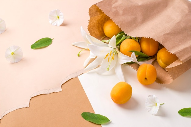 Ripe apricots and lily flowers in a kraft paper bag on a beige background