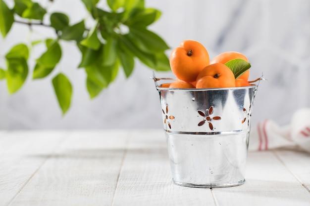 Спелые абрикосы с листьями в металлическом ведре на белом деревянном столе с копией пространства