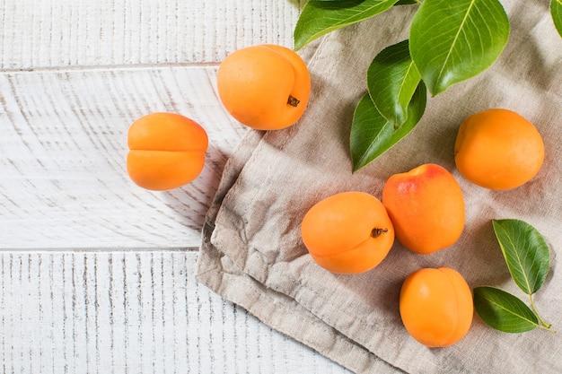 Спелые абрикосы с листьями на белом деревянном столе