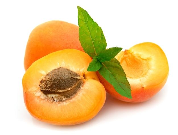 Спелые абрикосы с косточкой и мятой на белом фоне
