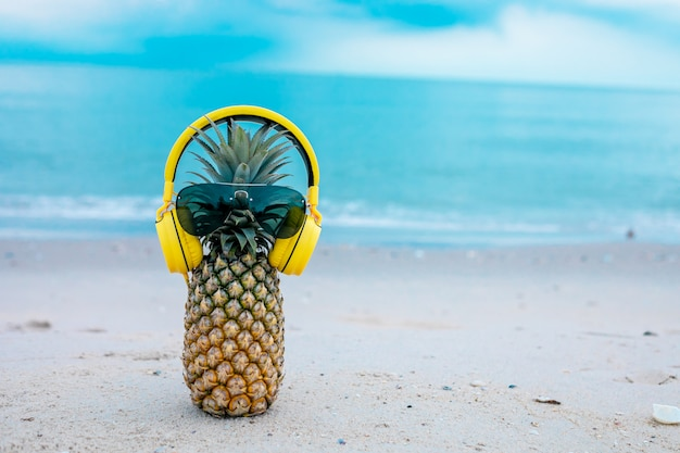 Ripe attractive pineapple in stylish mirrored sunglasses and gold headphones on sand against turquoise sea water. tropical summer vacation concept.