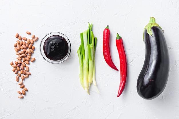Зрелые ингридиенты баклажана, для варить или гриль перец, баклажан, соус, гайки на белом взгляд сверху предпосылки.