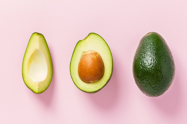 Ripe avocado on pink background - whole and cut fresh green fruit with seed on pastel
