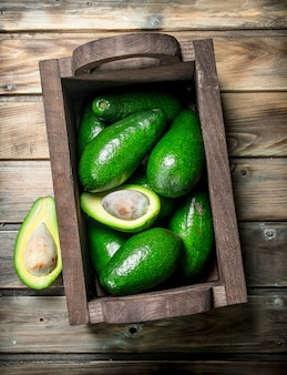 Ripe avocado in a wooden box. on a brown wooden.