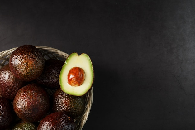 Ripe avocados in a basket on a black table, with a cut fruit and a stone