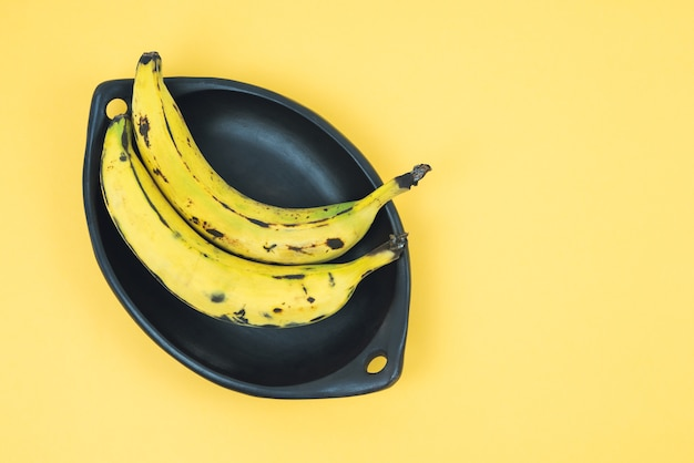 Ripe banana in a black bowl on a yellow background. copy space.