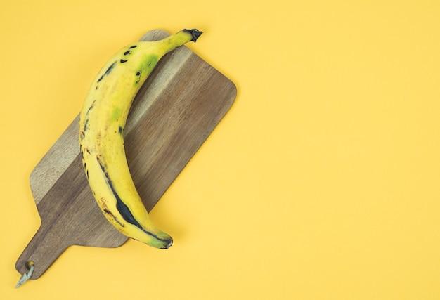 Спелый банан на желтом фоне