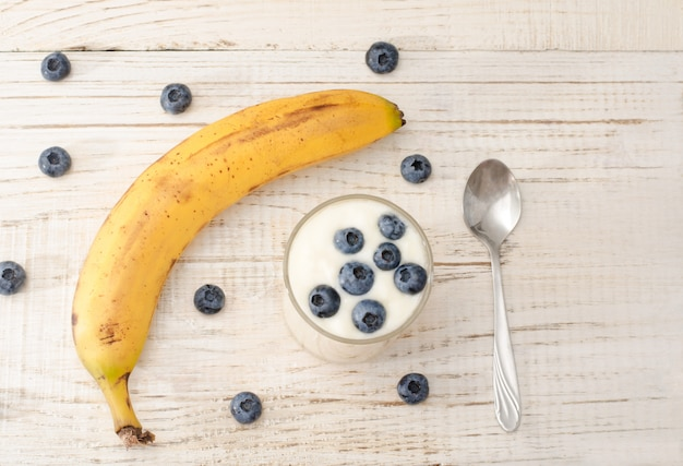 Ripe banana, yogurt with blueberries and spoon, wooden light table