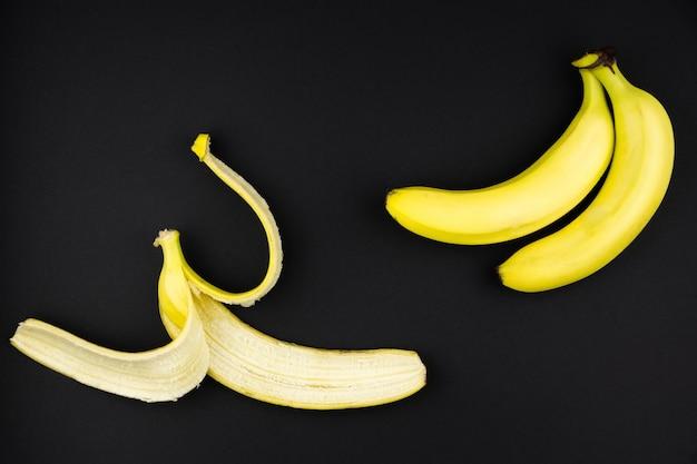 Спелые бананы и банановая кожура лежат на черном фоне