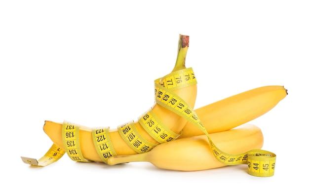 熟したバナナと白い背景の上の巻尺。減量の概念
