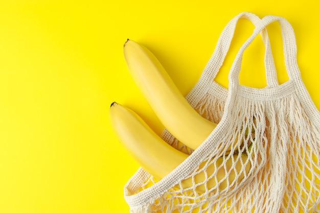 노란색 배경에 메쉬 가방에 익은 바나나 친환경 면 쇼핑백 유기농 과일