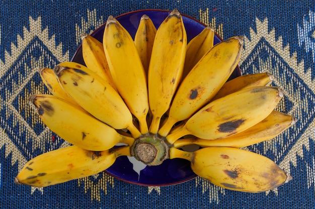 平らなプレートで熟したバナナはモザイクキリムに横たわっていた