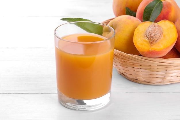 Спелые большие персики в корзине и стакан сока на белом деревянном фоне крупным планом.