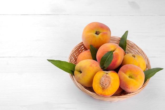 Спелые большие персики в корзине на белом деревянном фоне крупным планом. с местом для надписи