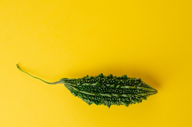 Ripe bitter gourd or momordica on yellow background with copy space.