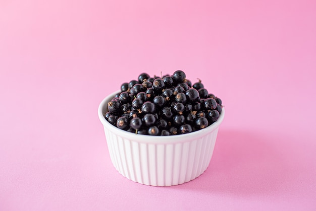 Ripe black currant or blueberries in a small white cup on pink