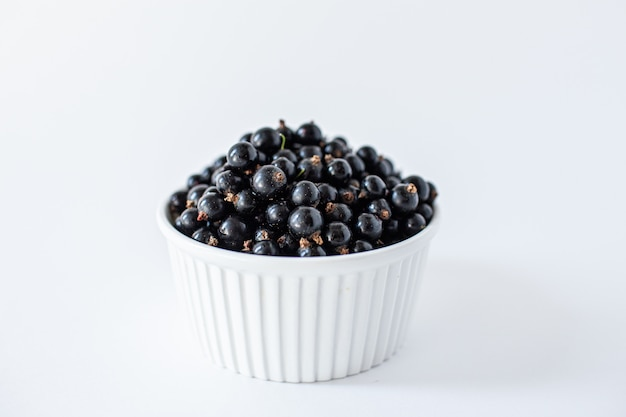 Ripe black currant or blueberries in a small white cup on white
