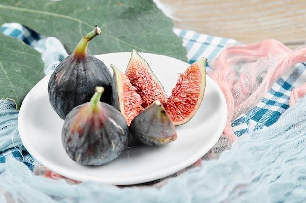 葉とテーブルクロスと白いプレート上の熟した黒いイチジク。