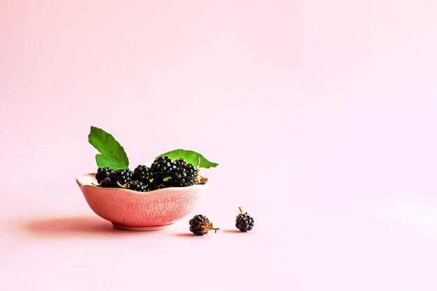 淡いピンクのパステルカラーの背景にピンクのボウルに葉を持つ熟したブラックベリー