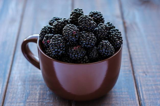 Ripe blackberry in a clay cup on a dark rustic table.