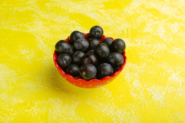 Ripe blackthorns inside red plate on yellow