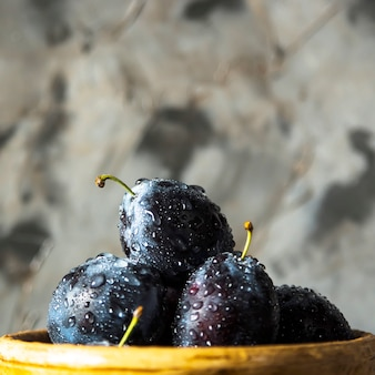 Ripe blue plums in a clay bowl on a gray table. summer seasonal fruit concept