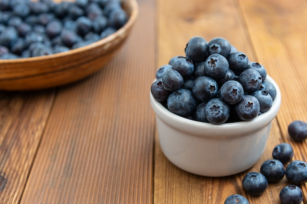 Ripe blueberries in the bowl on the wooden table, fresh berries for breakfast.