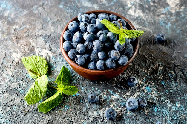Ripe  blueberries in ceramik bowl with leaves mint on a dark concrete background