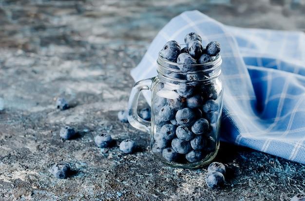 暗いコンクリートの背景にミントの葉とガラスの瓶に熟したブルーベリー